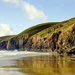 Chapel Porth Beach at low tide with Towanroath engine house perched on the cliff, St Agnes, Cornwall, UK